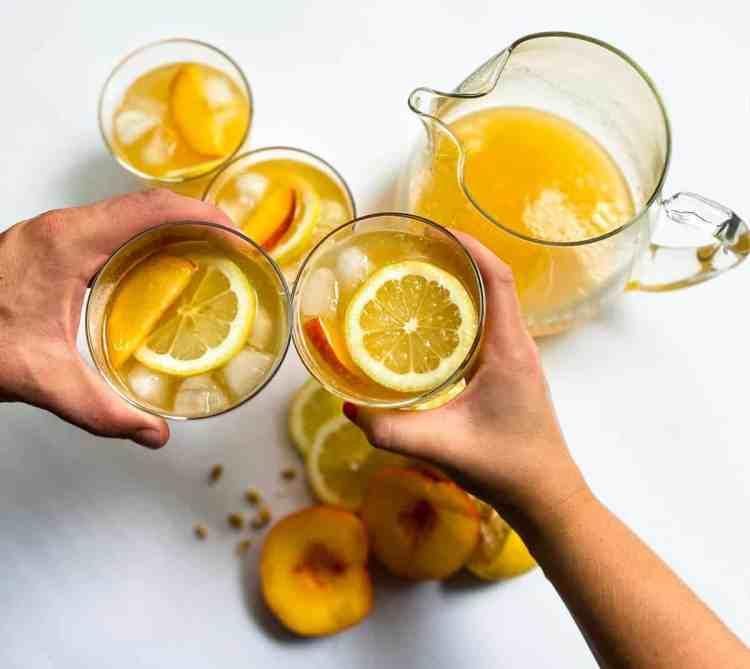 """Two hands """"cheersing"""" peach lemonade in cups"""