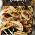 Chicken Dumplings on a wooden tray with chopsticks, scallions, and sesame soy dipping sauce.