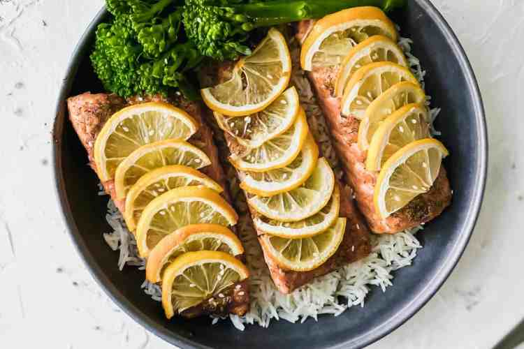 baked teriyaki salmon on top of white rice with broccoli in a black bowl.