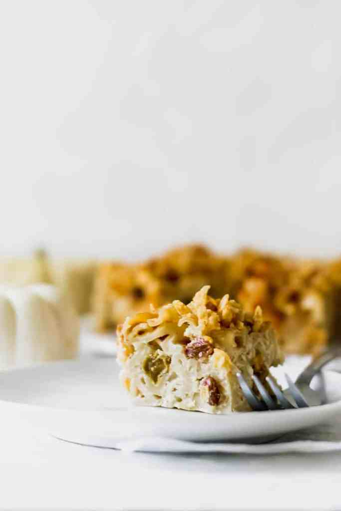 Up close view of a slice of kugel with a fork next to it.