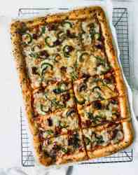 cooked mushroom, sausage, and arugula pizza on a cooling rack