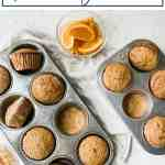 spiced orange muffins in a muffin pan with coarse sugar and orange slices.
