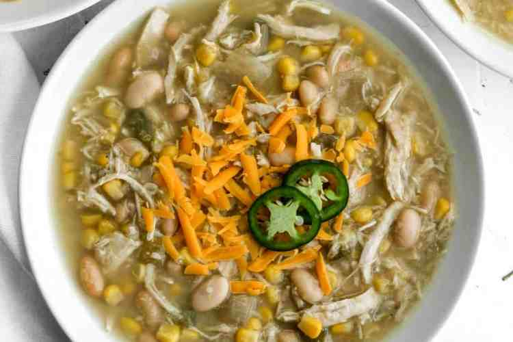 Healthy chicken chili in a white bowl with silver spoons and 3 additional bowls surrounding it.