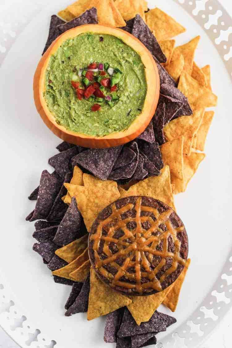 Guacamole and black bean dip in pumpkins on a white platter with a swirl of tortilla chips between.