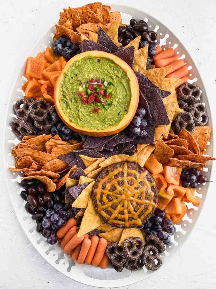 Halloween snack board on a large white platter with guacamole in a pumpkin and warm black bean dip.