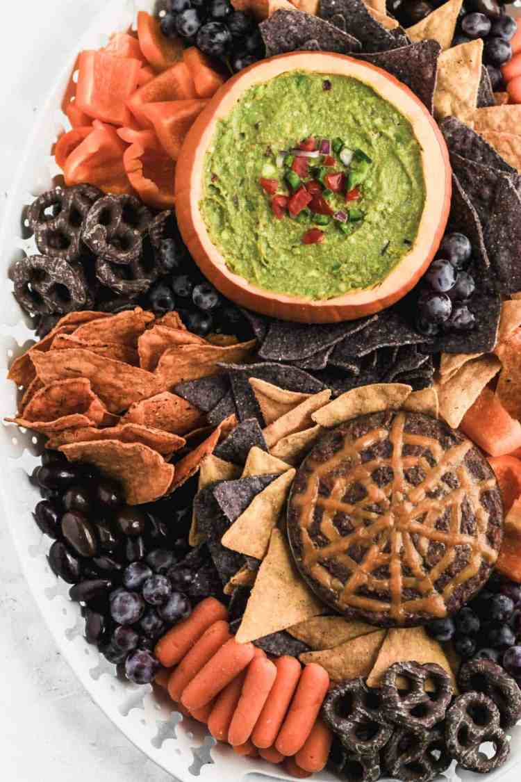 Halloween inspired guacamole snack board with dips, chips, chocolate almonds, carrots, peppers, chocolate pretzels, chocolate almonds, and grapes on a white platter.