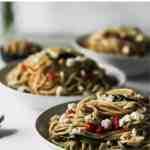 Mediterranean garlic and olive oil pasta in white bowls.