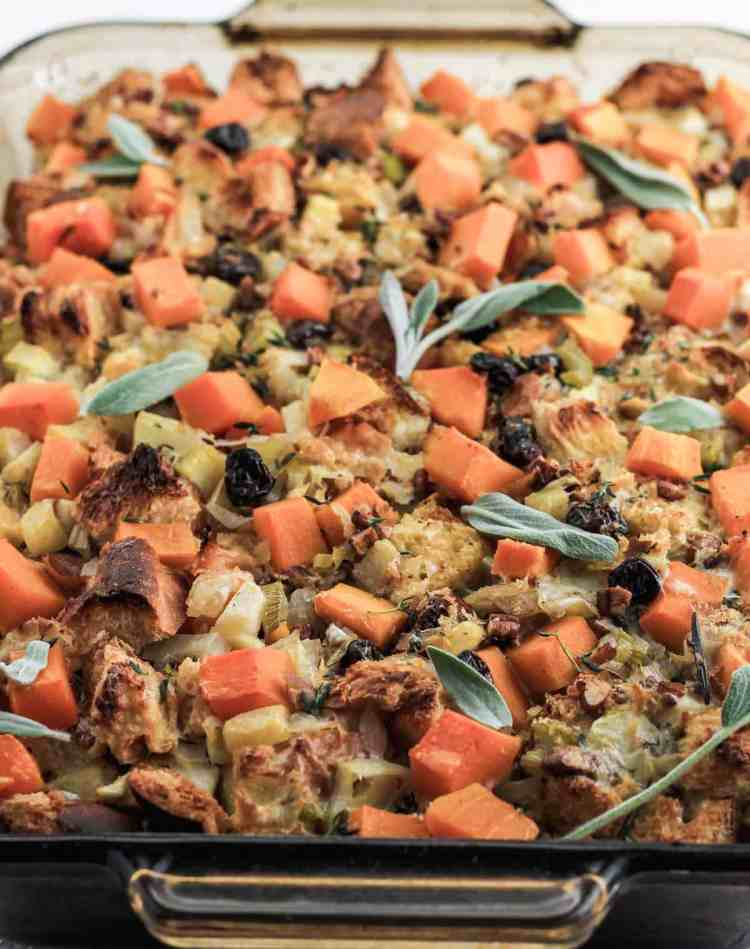 Butternut squash stuffing in a glass baking dish with leaves of sage on top.