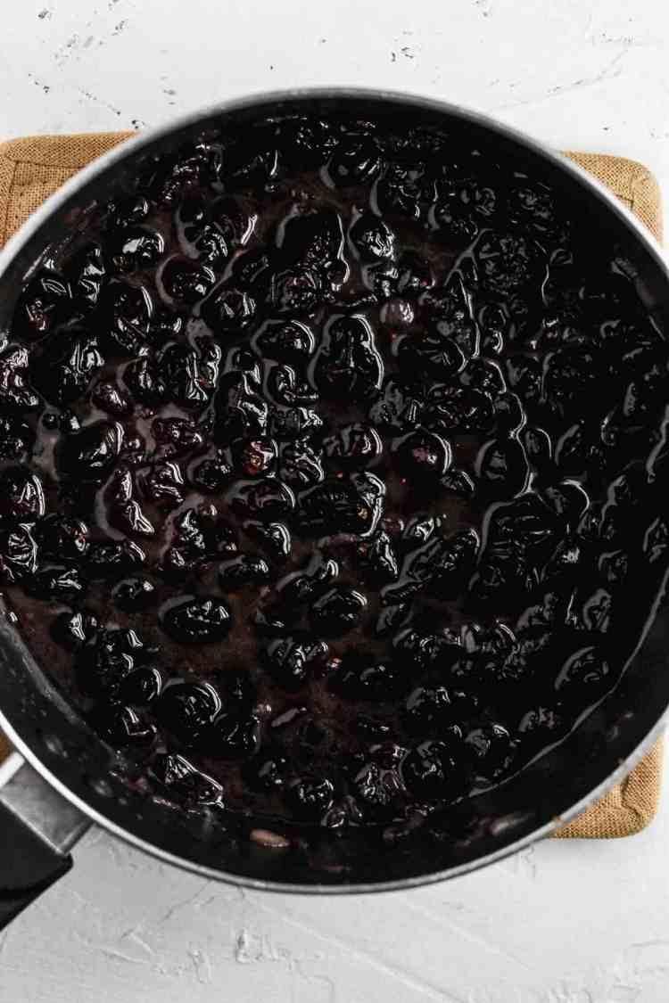 Warm cranberry vinaigrette cooking in a black saucepan.