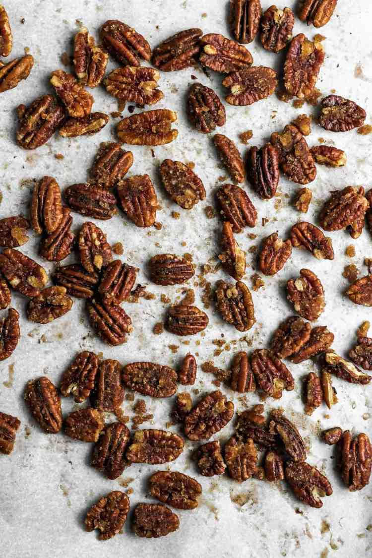Candied pecans on a sheetpan covered with parchment paper.