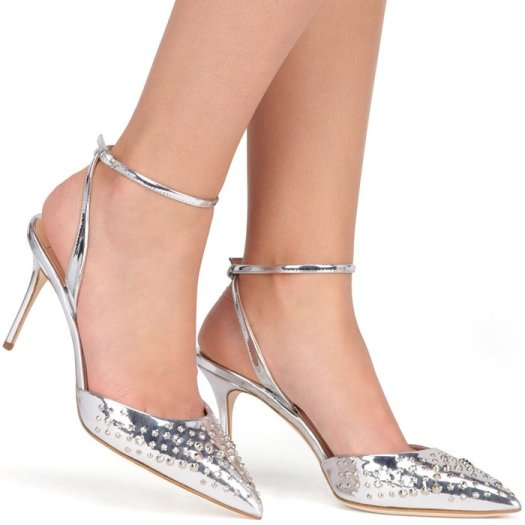 The mirrored silver leather is studded across the pointed toes, with low-slung uppers and a heel-fastening strap creating a streamlined silhouette