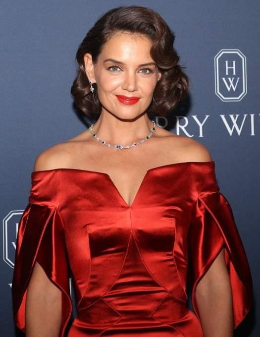 Katie Holmes wearinga shiny red silk cocktail dress by Zac Posen