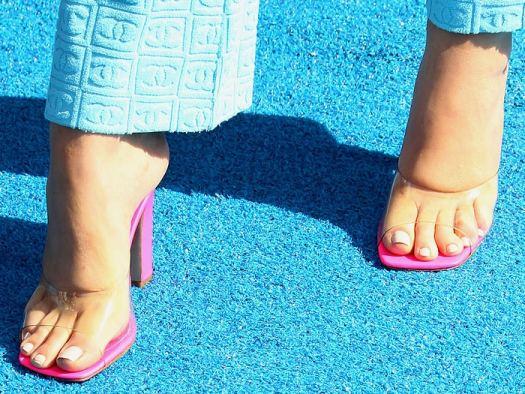 Maddie Ziegler's feet in pink clear-strap mules