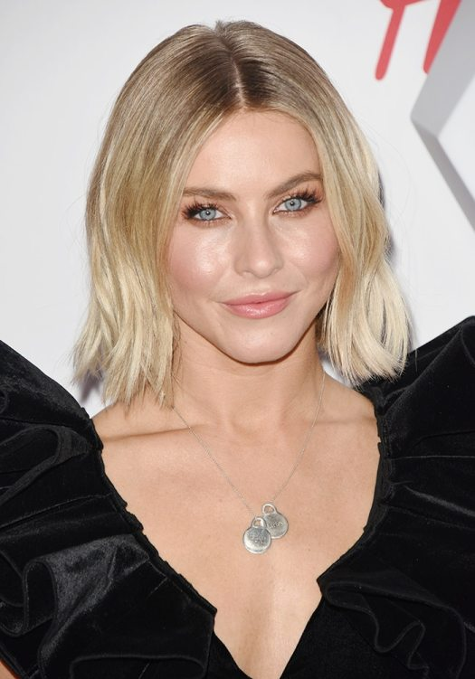 Julianne Hough styles her short blonde hair in subtle waves and applies pink-hued makeup on her face