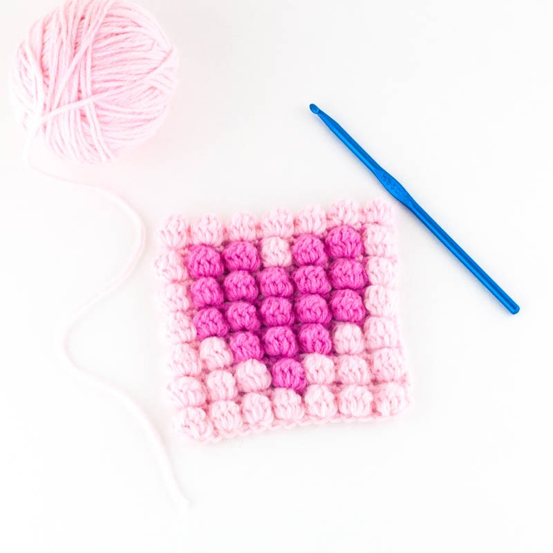Pink ball of yarn with a blue crochet hook and two-toned pink square with a heart