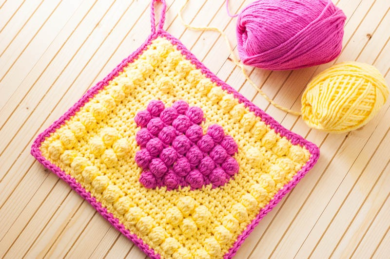 two skeins of pink and yellow cotton yarn with a yellow crochet potholder that has a pink heart in the center