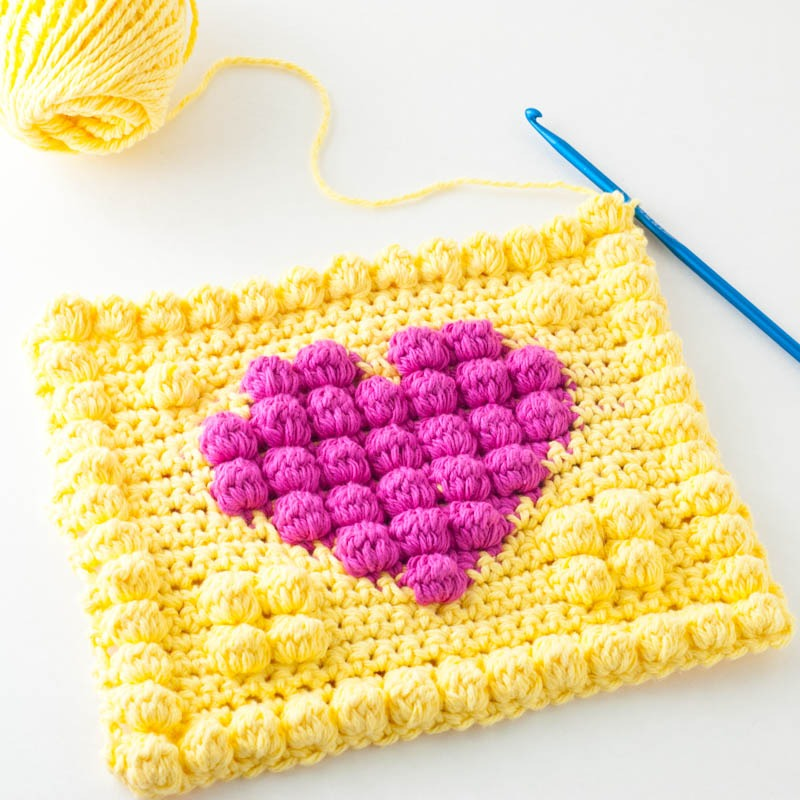 Completed body portion of the bobble heart potholder with a blue crochet hook and skein of yellow yarn