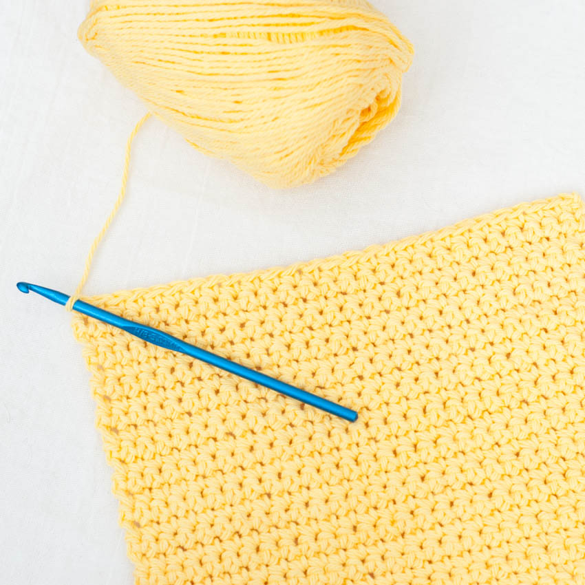 view of the yellow back piece of the bobble heart potholder, includes a skein of yarn and a blue crochet hook