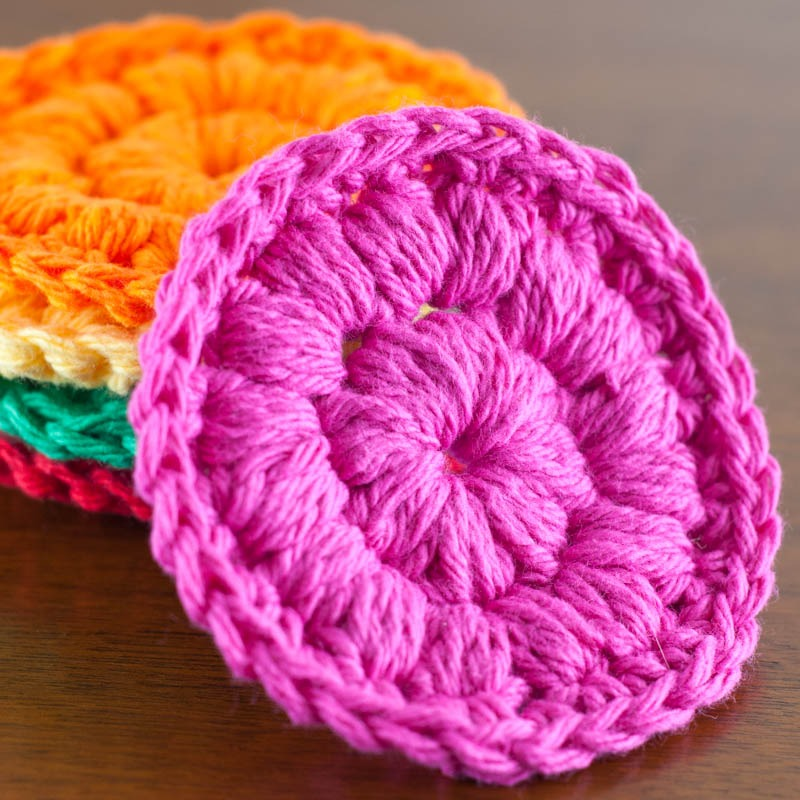 stack of colorful cotton face scrubbies with a pink crochet face scrubby leaning against it
