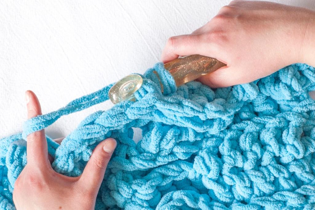 Hands crocheting a blue chunky throw