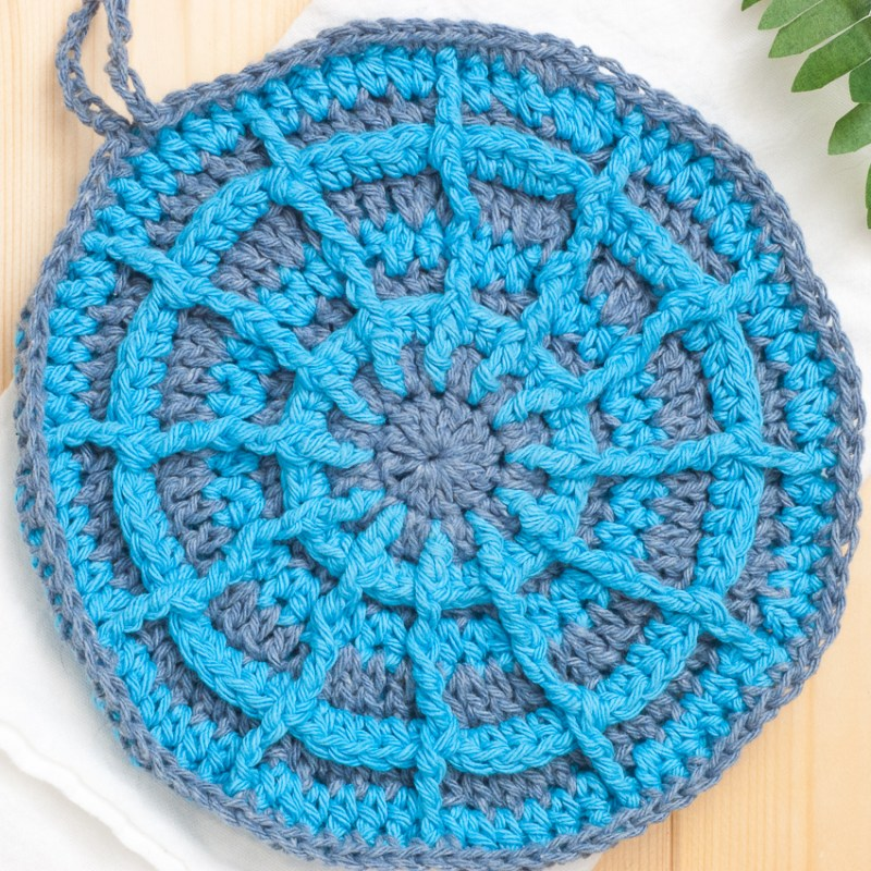Round crocheted potholder in blue