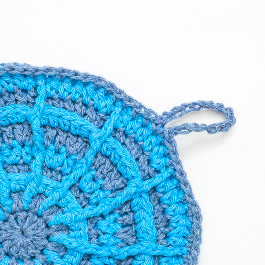 Close-up view of a blue crocheted potholder