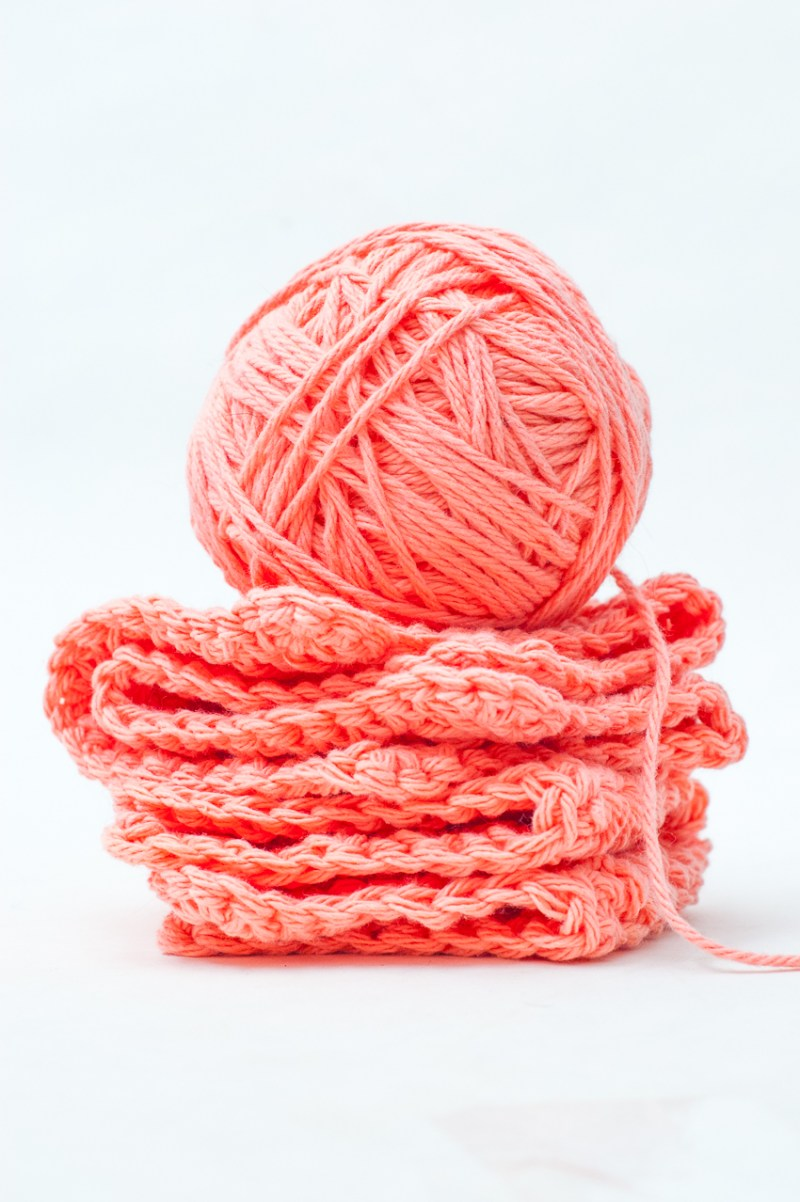 Two coral-colored crochet dishcloths with a ball of yarn on top