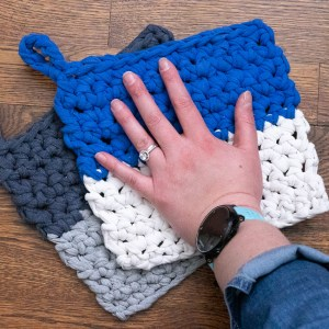 two crocheted potholders and a human hand