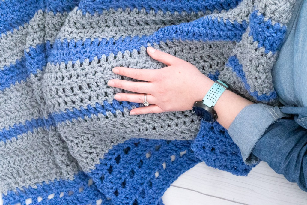 seated person covered by blue and grey crocheted blanket