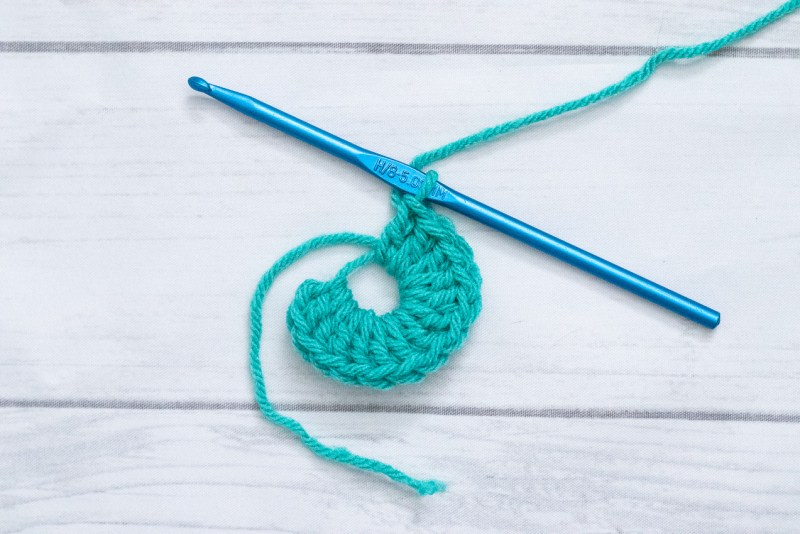 teal yarn and a blue crochet hook crocheting into a magic ring