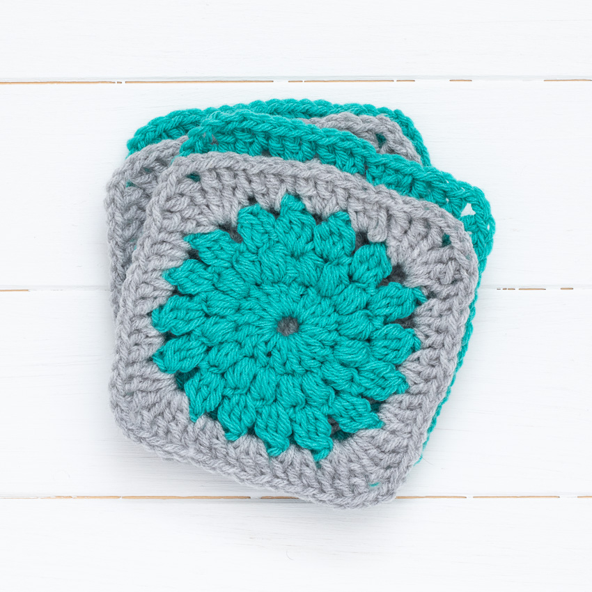 stack of four grey and teal sunburst granny squares on a white wood background