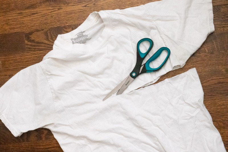 white t-shirt with the sleeves being cut off by black and green scissors