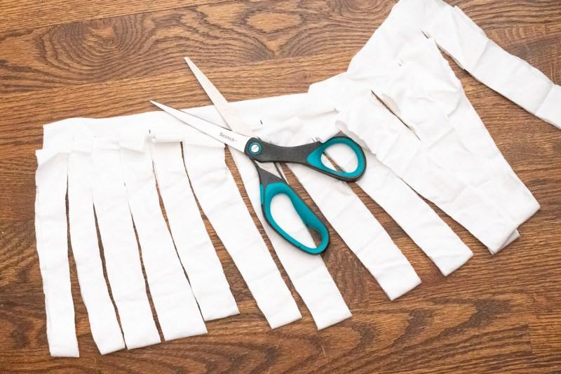white shirt being cut into 1-inch strips of fabric, scissors on top