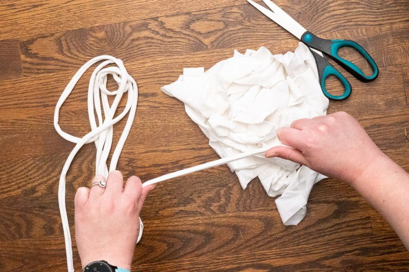 pile of white fabric strips being stretched into t-shirt yarn by two hands