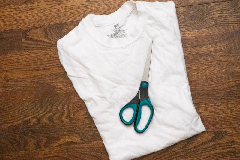 Plain white t-shirt and scissors on a hardwood floor
