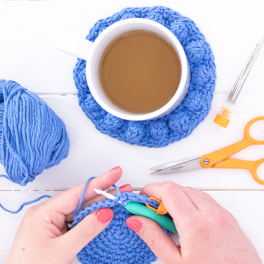 hands crocheting a coaster with scissors, yarn, tapestry needles, and a mug in the background