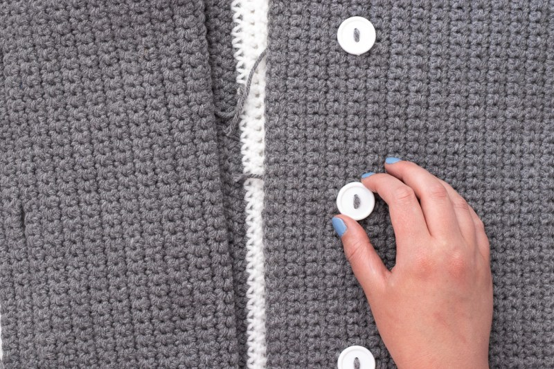grey crocheted pieces with a hand and three white buttons