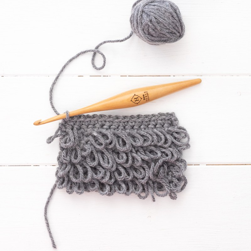 small swatch of loop stitches, a grey yarn ball, and a wooden crochet hook