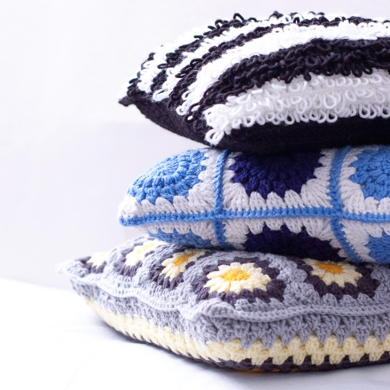 stack of three crocheted pillows