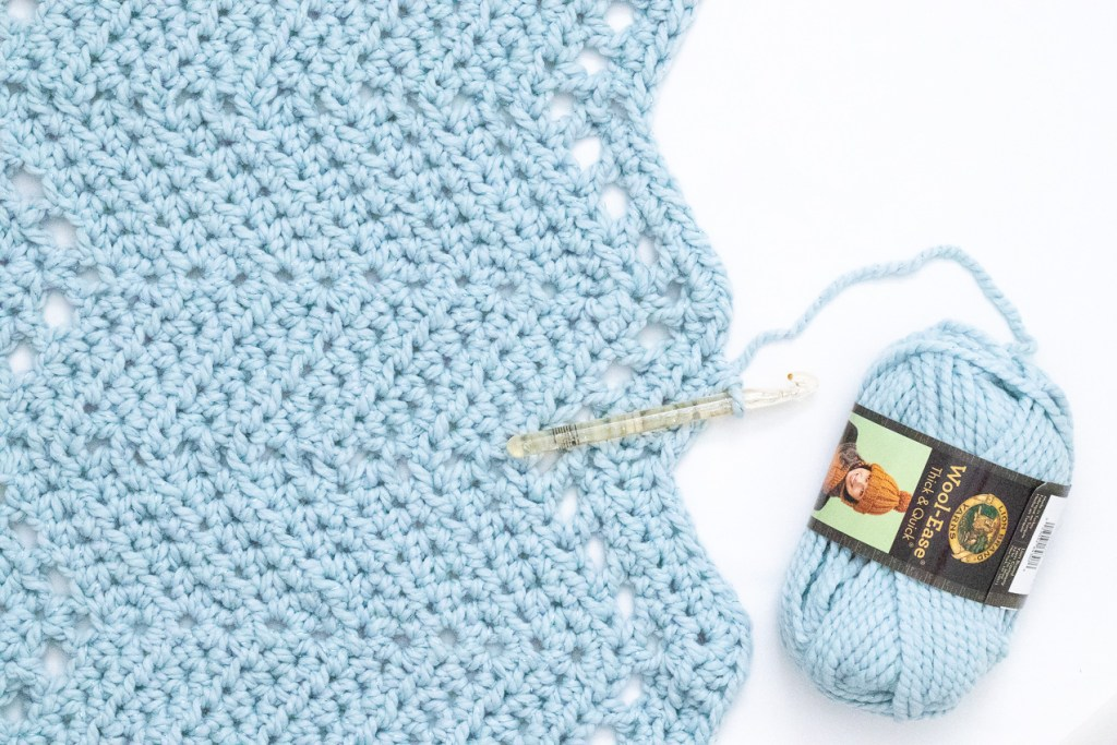 blue chunky crocheted ripple blanket with a yellow hook and a skein of wool-ease thick & quick yarn