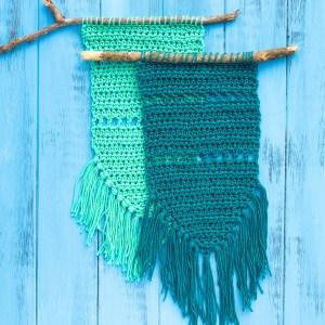 two crocheted simple fringed wall hangings on a blue wooden background