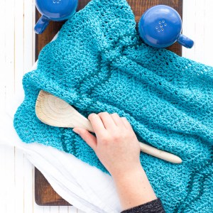 hand holding a wooden spoon on top of a crocheted ripple dish towel