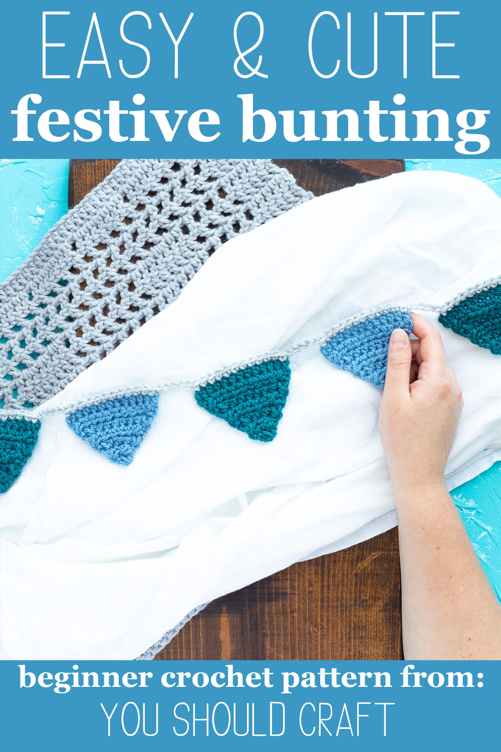 "hand holding a blue crocheted banner on  a white, wood, and blue background with text ""easy & cute festive bunting - beginner crochet pattern from: you should craft"""