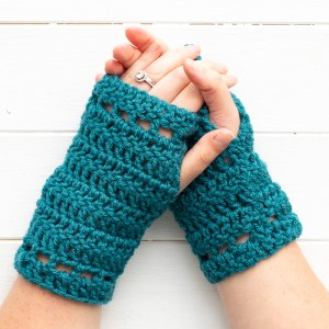 two folded hands wearing teal fingerless gloves on a white wooden background