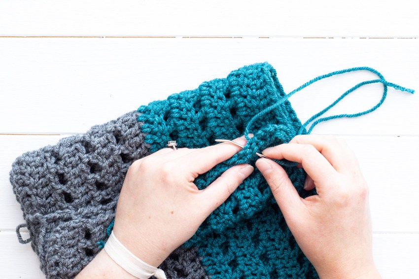 two hands sewing the seam of a crocheted color-blocked infinity scarf