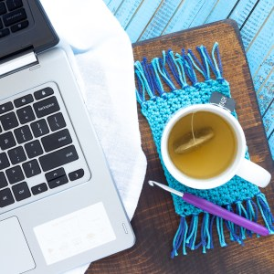 flat lay with a computer, mug of tea, purple crochet hook, and blue fringed mug rug