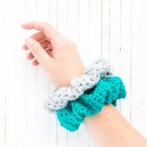 arm with teal and grey crocheted hair scrunchies