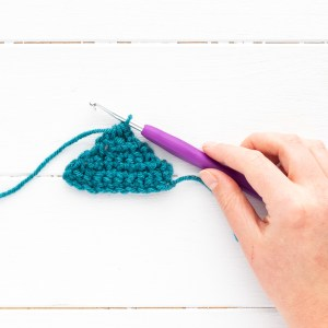 hand holding a purple crochet hook with a small teal crocheted triangle