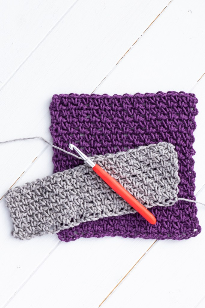 vertical image featuring a red crochet hook, grey in-progress swatch, and a purple linen stitch dishcloth