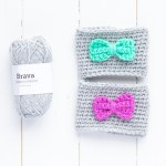 two coffee sleeves with bows and a small skein of grey brava yarn